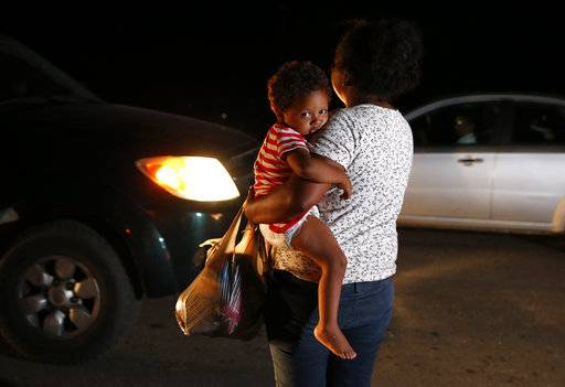 Honduran migrant Luz Padilla Valverde, carrying her child, begs for contributions of one peso (5 cents) from passing drivers, as a thousands-strong caravan of Central Americans hoping to reach the U.S. border stops for the night, in Matias Romero, Oaxaca state, Mexico, Thursday, Nov. 1, 2018. Most of the main caravan of Central American migrants spent a rain-drenched night outside, before continuing their slow walk through southern Mexico.