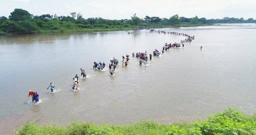 Salvadoran migrants cross the Suchiate river, the border between Guatemala and Mexico, on Friday, Nov. 2, 2018. A new group of Central American migrants has started on its way North with the stated purpose to make to the United States. The third caravan tried to cross the bridge between Guatemala and Mexico, but Mexican authorities told them they would have to show passports and visas and enter in groups of 50 for processing. The Salvadorans expressed misgivings that they would be deported, so they turned around and waded across a shallow stretch of the river to enter Mexico.