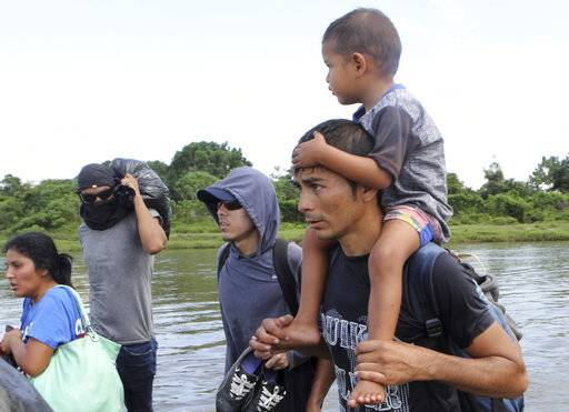 Salvadoran migrants cross the Suchiate river, the border between Guatemala and Mexico, on Friday, Nov. 2, 2018. A new group of Central American migrants has started on its way North with the stated purpose to make to the United States. The new caravan tried to cross the bridge between Guatemala and Mexico, but Mexican authorities told them they would have to show passports and visas and enter in groups of 50 for processing. The Salvadorans expressed misgivings that they would be deported, so they turned around and waded across a shallow stretch of the river to enter Mexico.