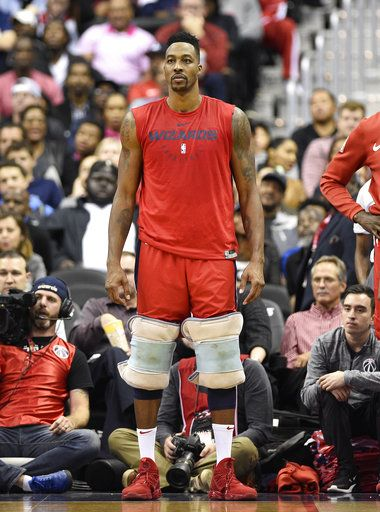 Washington Wizards center Dwight Howard watches from the sidelines with his knees wrapped during the second half of the team's NBA basketball game against the Oklahoma City Thunder, Friday, Nov. 2, 2018, in Washington.
