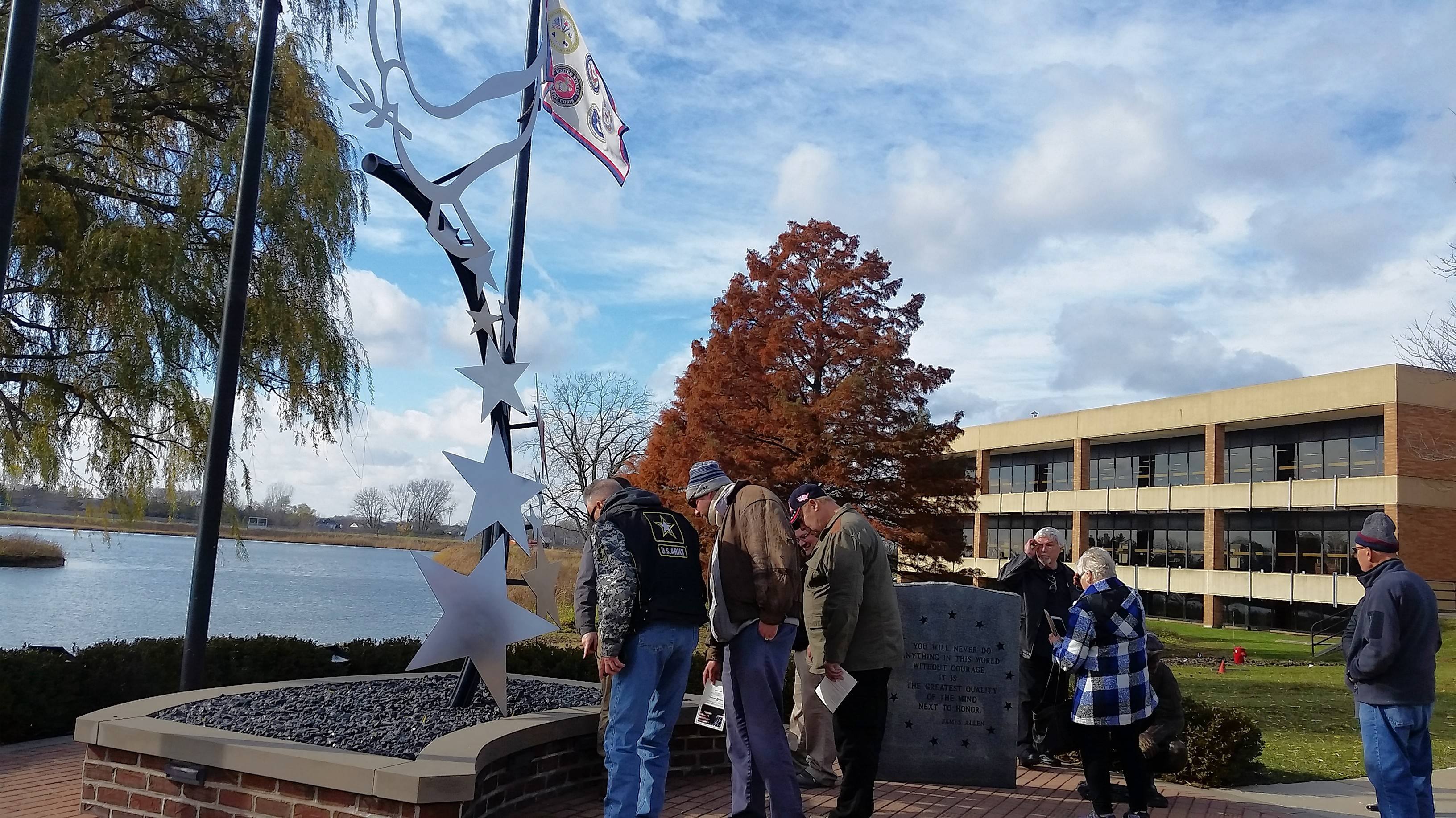"Wayne J. Maczko, left, and other veterans stand in front of a new 14-foot-tall statue titled ""Defenders of Peace."" The statue was one of two dedicated at a ceremony at the College of Lake County in Grayslake Monday."