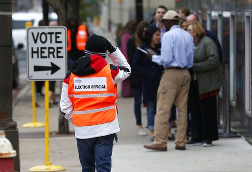 An election official, left, maintains the crowd line and parking spaces as people line up to vote at the Minneapolis Early Vote Center on the last day of early voting Monday, Nov. 5, 2018, in Minneapolis. The Associated Press will debut a new survey of the nation's electorate that aims to more accurately capture the story of how Americans vote and why in Tuesday's midterm elections.