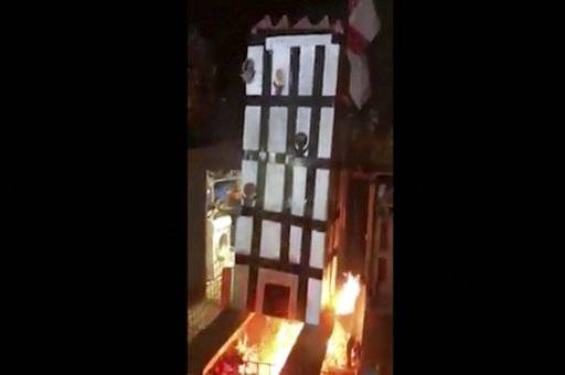 In this grab taken from video, made available on Tuesday, Nov. 6, 2018, people place a model of Grenfell Towers onto a bonfire, in London. London police have arrested five people over a video that showed a cardboard model of Grenfell Tower being burned on a bonfire - a video that shocked the families of the 72 victims who died in the 2017 inferno that engulfed the apartment block. (UGC via AP)