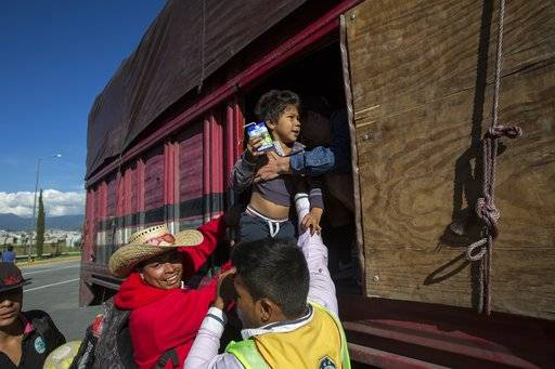 A boy is taken from a truck as Central American migrants arrive at the outskirts of Mexico City, Monday, Nov. 5, 2018. A big group of Central Americans pushed on toward Mexico City from a coastal state Monday, planning to exit a part of the country that has long been treacherous for migrants seeking to get to the United States.