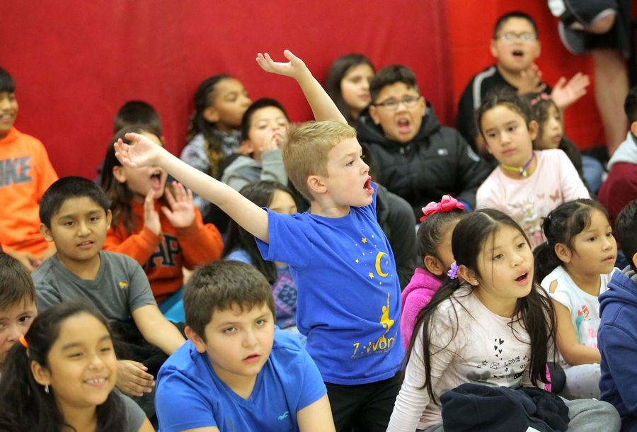 Kids cheer Wednesday as second grade bilingual teacher Christine Forster receives a check for $20,000 on behalf of Symetra and the Chicago Bears at Ellis Elementary school in Round Lake Beach.