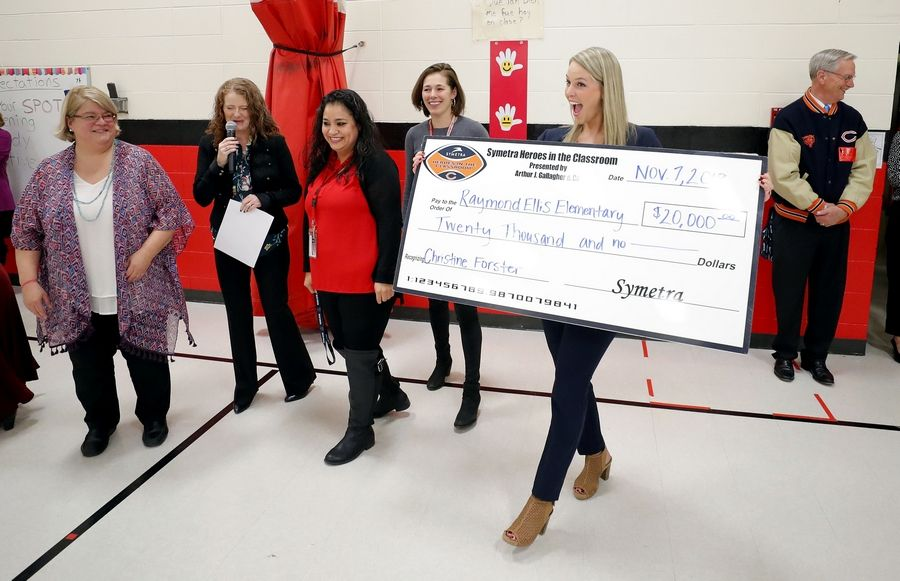 Kelly Lomas of Arthur J. Gallagher, right, presents a $20,000 check on behalf of Symetra and the Chicago Bears to Ellis Elementary school Wednesday in Round Lake Beach.