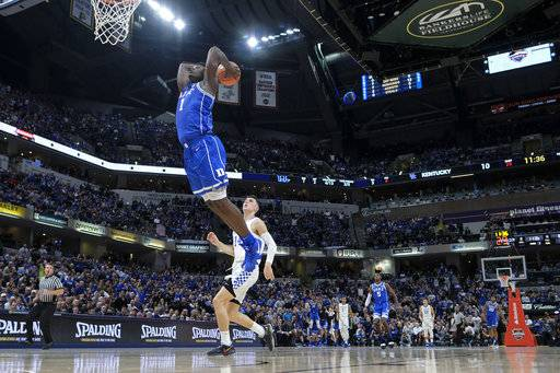 Duke forward Zion Williamson (1) goes up for a dunk in front of Kentucky guard Tyler Herro during the first half of an NCAA college basketball game at the Champions Classic in Indianapolis on Tuesday, Nov. 6, 2018.
