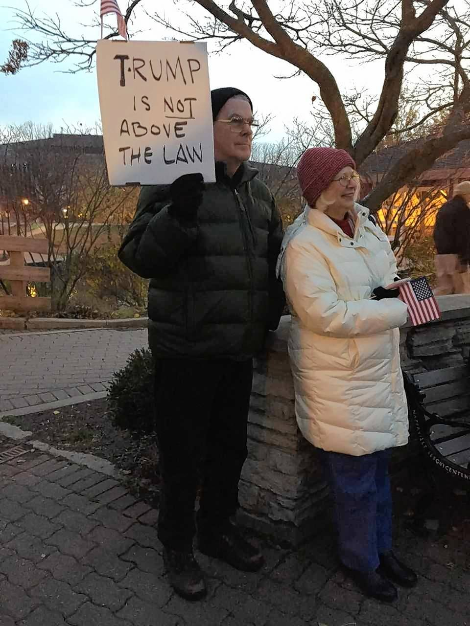 "Chuck and Susan Cornell of Romeoville protest Thursday afternoon in downtown Naperville as part of a crowd of 400 people unhappy with the forced resignation of former U.S. Attorney General Jeff Sessions. ""I feel Trump's been trying his best to ruin our country,"" Chuck Cornell said, ""and this is another step, which is dangerous."""