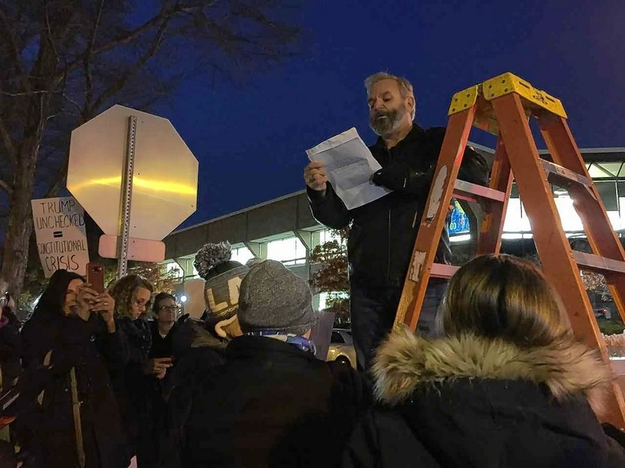 Naperville protest organizer Bob Landolti reads from the Declaration of Independence on Thursday afternoon as he launches a protest among a crowd of about 400 people unhappy with the forced resignation Wednesday of former U.S. Attorney General Jeff Sessions.