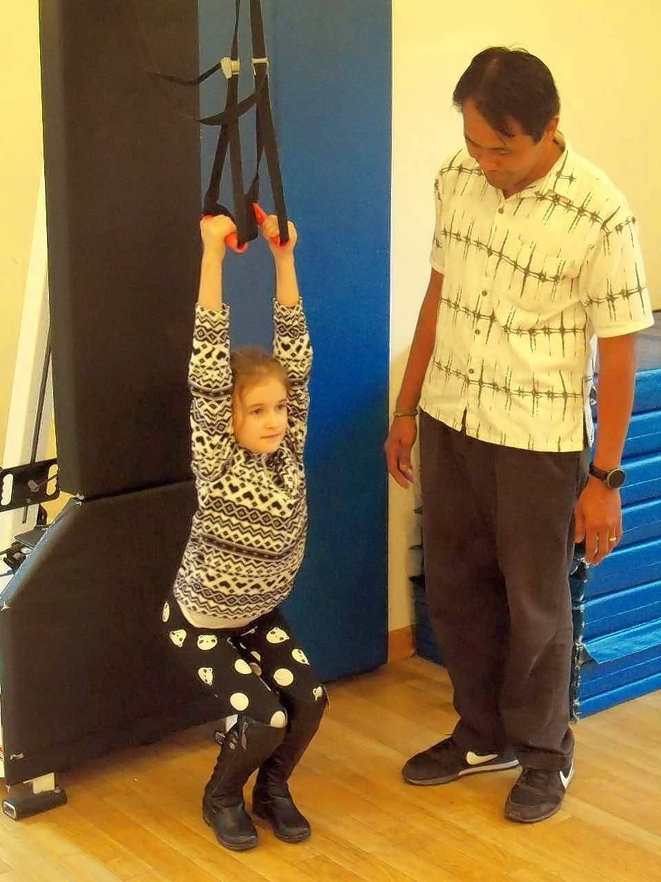 Seven-year-old Ariel Panteleeva of Arlington Heights demonstrates a pullup activity supervised by Riverwoods Montessori Teacher Freddie Madrid of Morton Grove.
