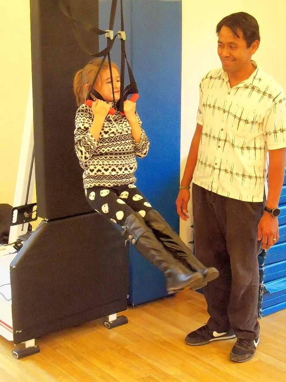 Seven-year-old Ariel Panteleeva of Arlington Heights demonstrates a pullup activity supervised by Riverwoods Montessori Teacher Freddie Madrid.