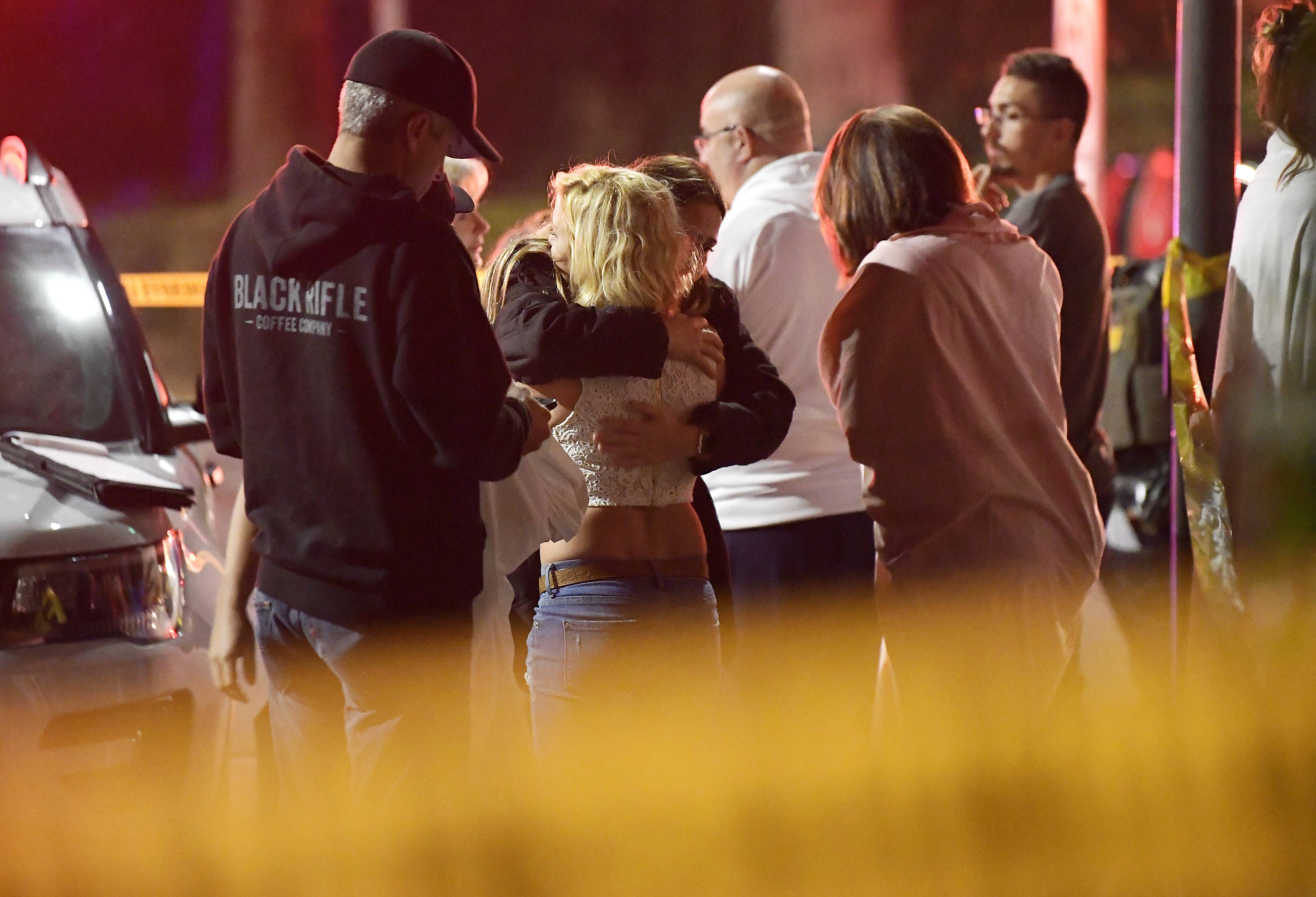 "People comfort each other Thursday as they stand near the scene in Thousand Oaks, California. where a gunman opened fire Wednesday inside a country dance bar crowded with hundreds of people on ""college night,"" wounding 11 people including a deputy who rushed to the scene. Ventura County sheriff's spokesman says gunman is dead inside the bar."