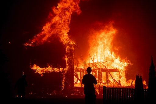 A home burns as the Camp Fire rages through Paradise, Calif., on Thursday, Nov. 8, 2018. Tens of thousands of people fled a fast-moving wildfire Thursday in Northern California, some clutching babies and pets as they abandoned vehicles and struck out on foot ahead of the flames that forced the evacuation of an entire town.