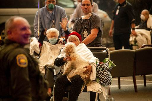 Medical personnel evacuate patients as the Feather River Hospital burns while the Camp Fire rages through Paradise, Calif., on Thursday, Nov. 8, 2018. Tens of thousands of people fled a fast-moving wildfire Thursday in Northern California, some clutching babies and pets as they abandoned vehicles and struck out on foot ahead of the flames that forced the evacuation of an entire town.