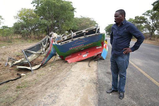 A man stands at the scene of a bus crash in Rusape about 170 kilomertes east of the capital Harare, Thursday, Nov. 8, 2018. A head-on collision between two buses has killed 47 people, where road accidents are common due to poor roads and bad driving.