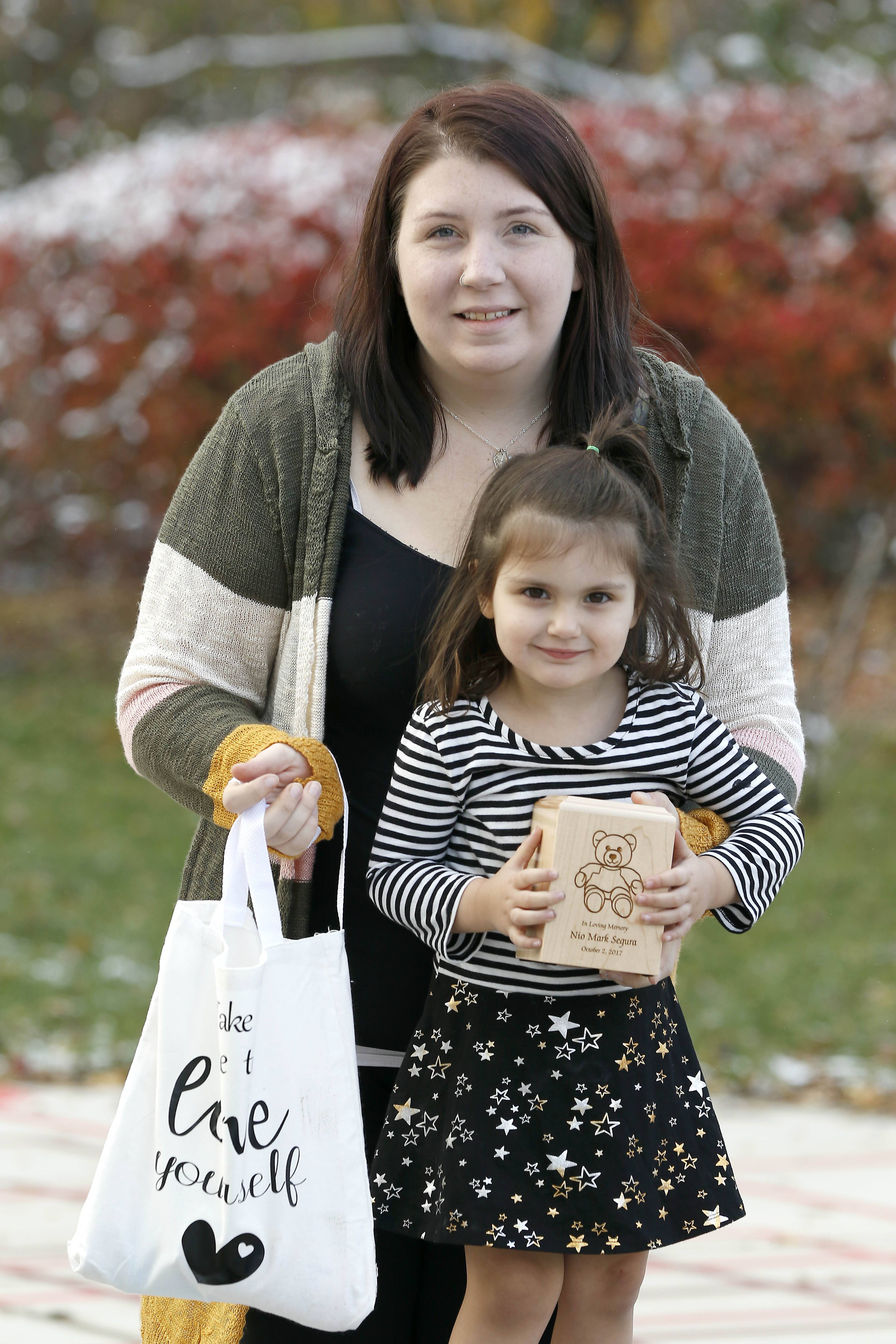 "Kelsey Funk, 28, of South Elgin delivered a stillborn baby boy, Nio, in October 2017 and recently formed the group ""Peace through Pain"" to help other women through trauma. She is pictured here with her daughter Luna Segura, 3, her son Nio's urn, and one of the ""love bags"" the group donates."