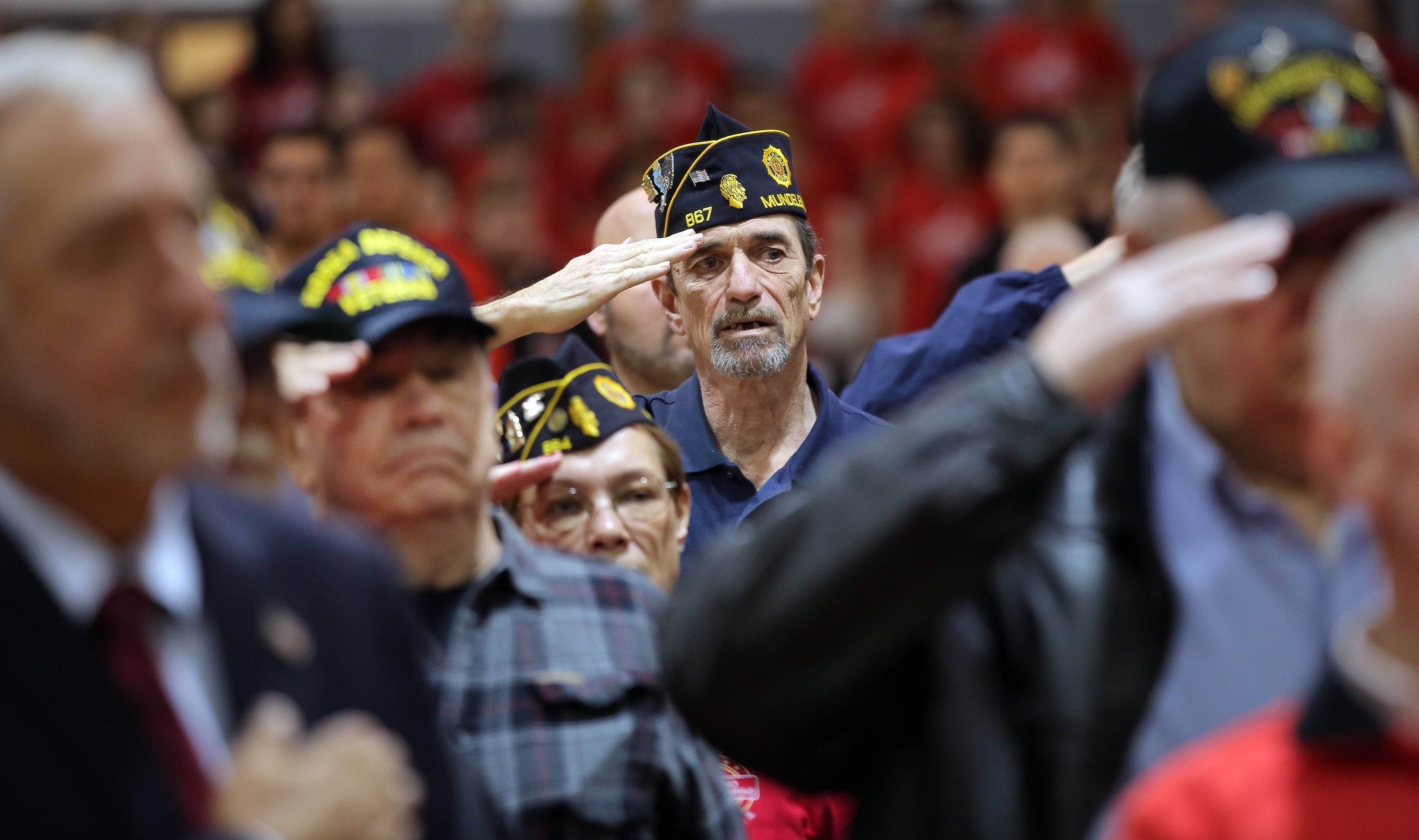 Veterans salute as the national anthem is played during a Veterans Day assembly at Mundelein High School Friday.