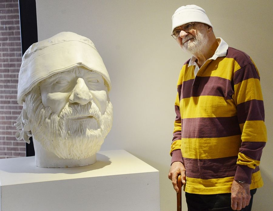 Bernie Bluestein stands next to a bust of himself that another student made, that was displayed at Harper College in Palatine.