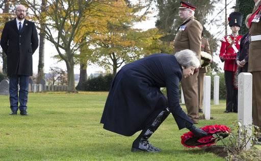 British Prime Minister Theresa May, center, and Belgian Prime Minister Charles Michel, left, lay wreaths at the graves of British World War I soldiers John Parr and George Ellison at the St. Symphorien cemetery in Mons, Belgium, Friday, Nov. 9, 2018. (Benoit Doppagne,Pool Photo via AP)
