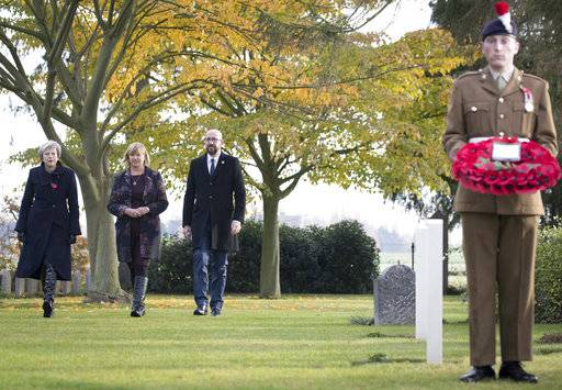 British Prime Minister Theresa May, left, and Belgian Prime Minister Charles Michel, second right, prepare to lay wreaths at the graves of British World War I soldiers John Parr and George Ellison at the St. Symphorien cemetery in Mons, Belgium, Friday, Nov. 9, 2018. (Benoit Doppagne,Pool Photo via AP)