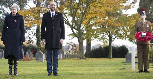 British Prime Minister Theresa May, left, and Belgian Prime Minister Charles Michel, center, prepare to lay wreaths at the graves of British World War I soldiers John Parr and George Ellison at the St. Symphorien cemetery in Mons, Belgium, Friday, Nov. 9, 2018. (Benoit Doppagne,Pool Photo via AP)