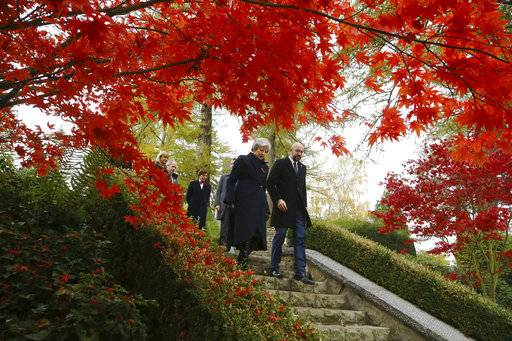 Britain's Prime Minister Theresa May and Belgian Prime Minister Charles Michel, right, walk through the St Symphorien Military Cemetery in Mons, Belgium, Friday Nov. 9, 2018, where wreaths were placed at the graves of John Parr, the first British soldier to be killed in WWI in 1914, and George Ellison, the last British soldier to be killed before Armistice in 1918. (Gareth Fuller/Pool via AP)