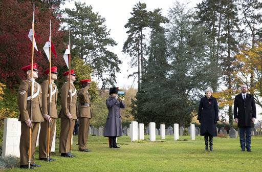 British Prime Minister Theresa May, second right, and Belgian Prime Minister Charles Michel, right, prepare to lay wreaths at the graves of British World War I soldiers John Parr and George Ellison at the St. Symphorien cemetery in Mons, Belgium, Friday, Nov. 9, 2018. (Benoit Doppagne, Pool Photo via AP)