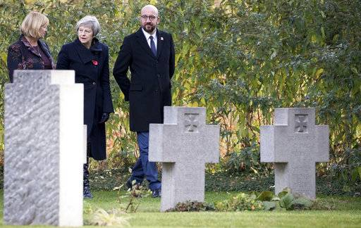 British Prime Minister Theresa May, center, and Belgian Prime Minister Charles Michel, right, walk among graves before laying wreaths at the graves of British World War I soldiers John Parr and George Ellison at the St. Symphorien cemetery in Mons, Belgium, Friday, Nov. 9, 2018. (Benoit Doppagne,Pool Photo via AP)