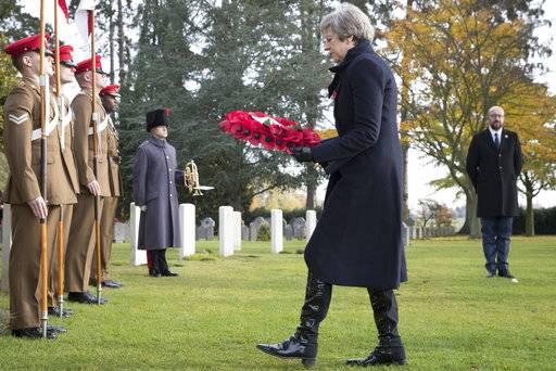 British Prime Minister Theresa May, center, and Belgian Prime Minister Charles Michel, right, lay wreaths at the graves of British World War I soldiers John Parr and George Ellison at the St. Symphorien cemetery in Mons, Belgium, Friday, Nov. 9, 2018. (Benoit Doppagne, Pool Photo via AP)