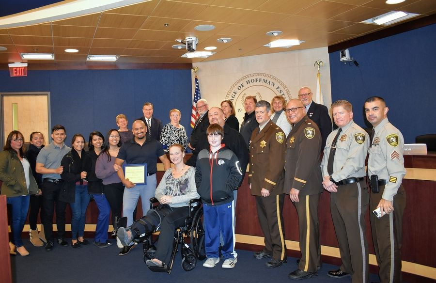 Ruben Xochihua, holding plaque, was recognized by Hoffman Estates and Cook County sheriff's officials last week for saving the life of Deputy Margie Sullivan, seated, who was involved in a traffic crash this summer.