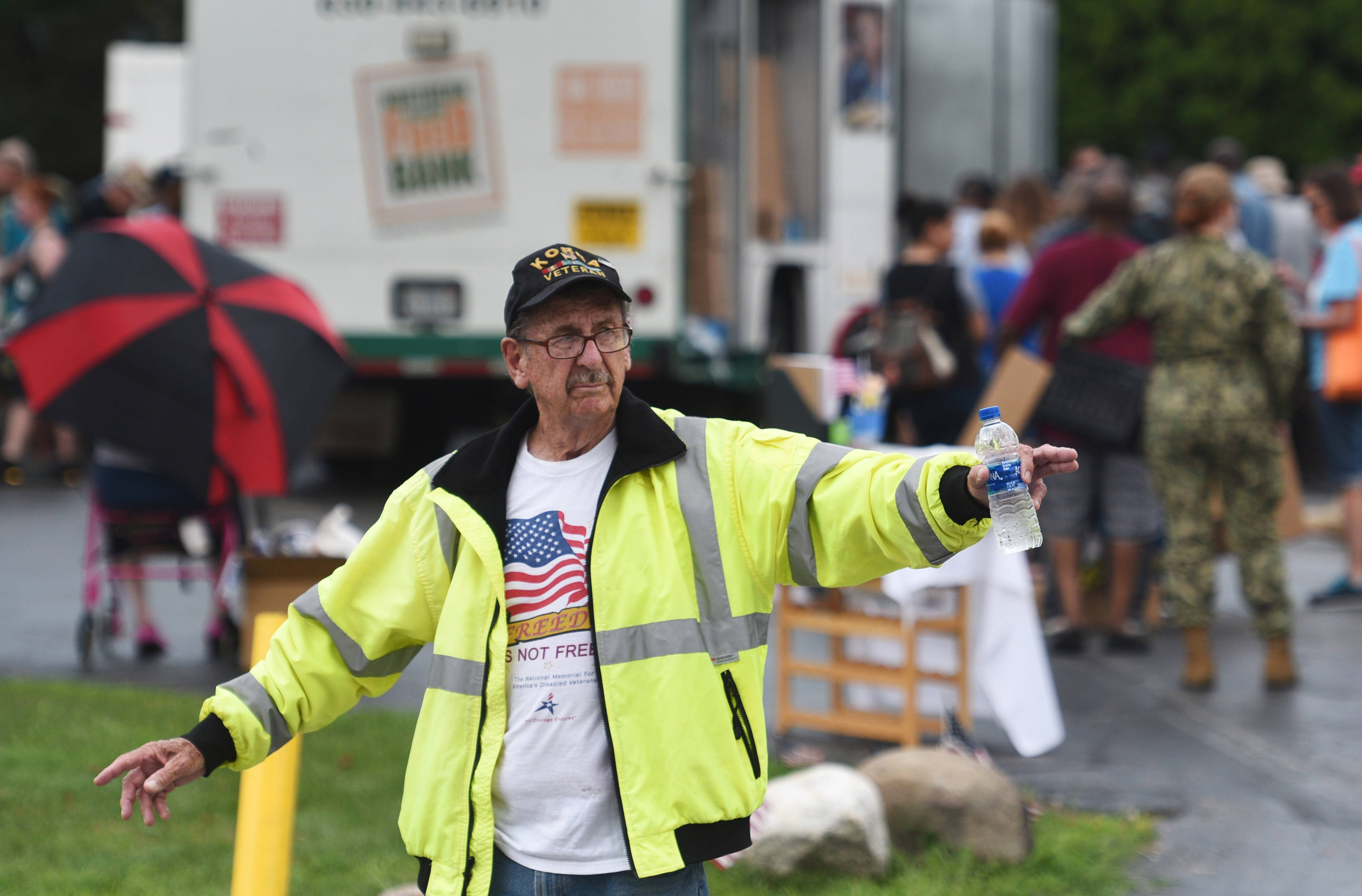"Russ ""Pops"" McCann, an 82-year Korean veteran from Des Plaines, directs traffic during a Northern Illinois Food Bank event at the Midwest Veterans Closet in North Chicago."