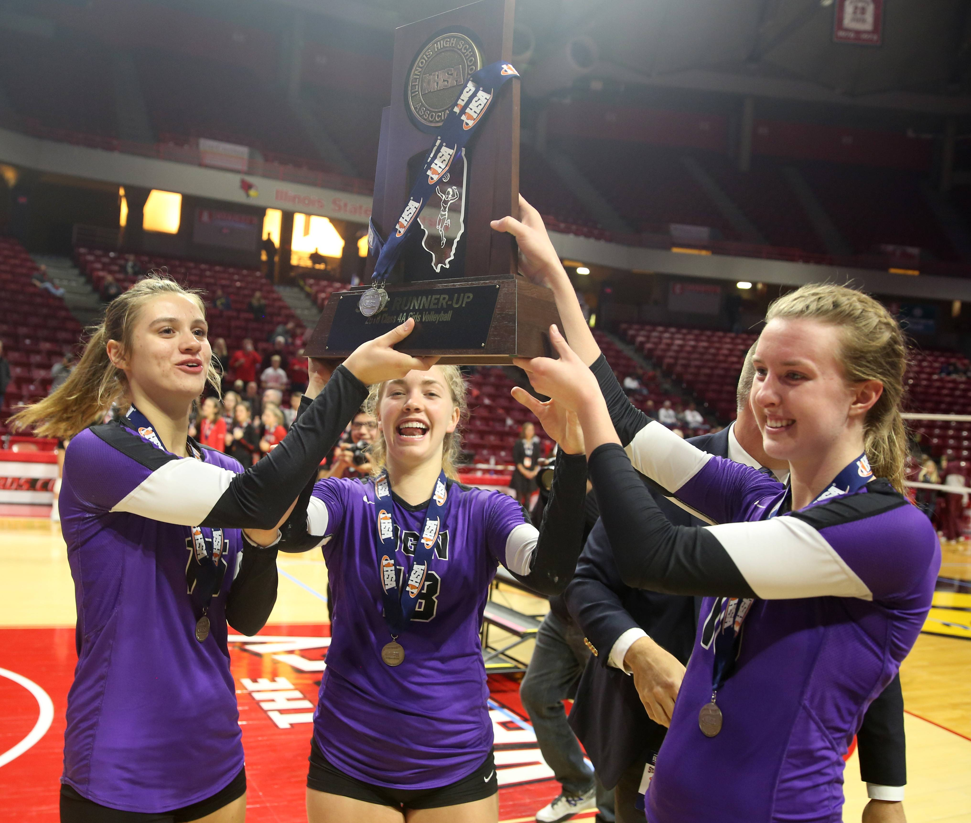 Downers Grove North players, from left, Maddie Degiorgio, Elizabeth Dunlap and Margaret Mahlke hoist their hardware during trophy presentations for the Class 4A state finals in girls volleyball on Saturday night at Redbird Arena on the campus of Illinois State University. The Trojans finished runners up to Marist.
