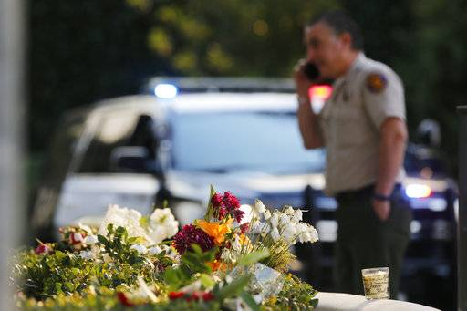 A bouquet of flowers, left by mourners, lays near the site of Wednesday's mass shooting, in Thousand Oaks, Calif., Friday, Nov. 9, 2018. Investigators continue to work to figure out why an ex-Marine opened fire Wednesday evening inside a Southern California country music bar, killing multiple people.