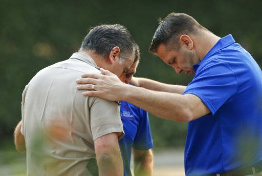 Ventura County Sheriff's Office Capt. Garo Kuredjian, left, embraces chaplains with the Billy Graham Rapid Response Team (RRT) as they pray near the site of Wednesday's mass shooting in Thousand Oaks, Calif., Friday Nov. 9, 2018. Investigators continue to work to figure out why an ex-Marine opened fire Wednesday evening inside a Southern California country music bar, killing multiple people.