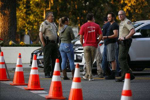 Thousand Oaks residents await to claim their vehicles as FBI agents verify vehicle registrations of autos parked in the lot of the Borderline Bar & Grill bar in Thousand Oaks, Calif., Friday, Nov. 9, 2018. The gunman who killed 12 people at the country music bar in Southern California went on social media during the attack and posted about his mental state and whether people would believe he was sane, a law enforcement official said Friday.