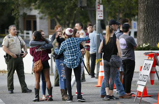 People hug as they arrive to recover their vehicles parked in the parking lot the Borderline Bar & Grill bar in Thousand Oaks, Calif., Friday, Nov. 9, 2018. The gunman who killed 12 people at the country music bar in Southern California went on social media during the attack and posted about his mental state and whether people would believe he was sane, a law enforcement official said Friday.
