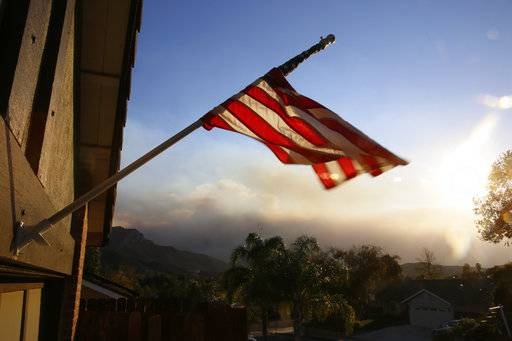 A flag is seen partially wrapped up in its pole due to heavy winds, outside the home of the ex-Marine Ian David Long, who killed 12 people at a country music bar Wednesday, in Newbury Park, Calif., Friday, Nov. 9, 2018. Wildfire smoke fills the sky in the background.