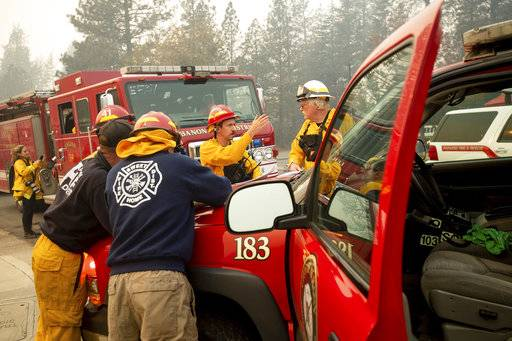 Firefighters plan their operations while battling the Camp Fire in Paradise, Calif., on Saturday, Nov. 10, 2018.  The blaze that started Thursday outside the hilly town of Paradise has grown and destroyed more than 6,700 buildings, almost all of them homes, making it California's most destructive wildfire since record-keeping began. But crews have made gains and the fire is partially contained, officials said Saturday.
