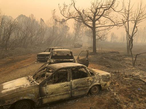 Burned out cars sit on the road side Saturday, Nov. 10, 2018, near Paradise, Calif., where the bodies of at least five people were found, officials said.