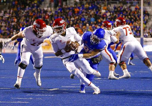 Fresno State quarterback Marcus McMaryion (6) tries to pull away from Boise State's Curtis Weaver (99) during the first half of an NCAA college football game Friday, Nov. 9, 2018, in Boise, Idaho. Weaver sacked McMaryion on the play.