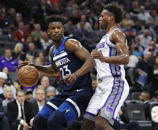 Minnesota Timberwolves guard Jimmy Butler (23) battles for position against Sacramento Kings guard Buddy Hield (24) during the first half of an NBA basketball game in Sacramento, Calif., Friday, Nov. 9, 2018.