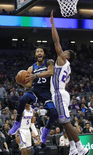 Minnesota Timberwolves guard Derrick Rose (25) drives to the basket against Sacramento Kings guard Buddy Hield (24) during the first half of an NBA basketball game in Sacramento, Calif., Friday, Nov. 9, 2018.