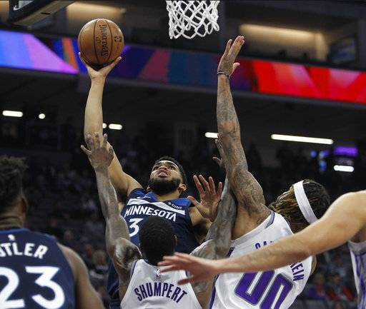 Minnesota Timberwolves center Karl-Anthony Towns (32) shoots over Sacramento Kings guard Iman Shumpert (9) and Sacramento Kings center Willie Cauley-Stein (00) during the first half of an NBA basketball game in Sacramento, Calif., Friday, Nov. 9, 2018.