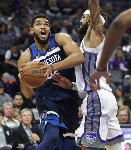 Minnesota Timberwolves center Karl-Anthony Towns (32) drives to the basket against Sacramento Kings center Willie Cauley-Stein (00) during the first half of an NBA basketball game in Sacramento, Calif., Friday, Nov. 9, 2018.
