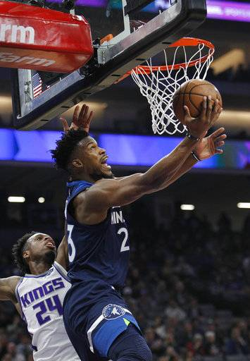 Minnesota Timberwolves guard Jimmy Butler (23) gets around Sacramento Kings guard Buddy Hield (24) for a basket during the first half of an NBA basketball game in Sacramento, Calif., Friday, Nov. 9, 2018.