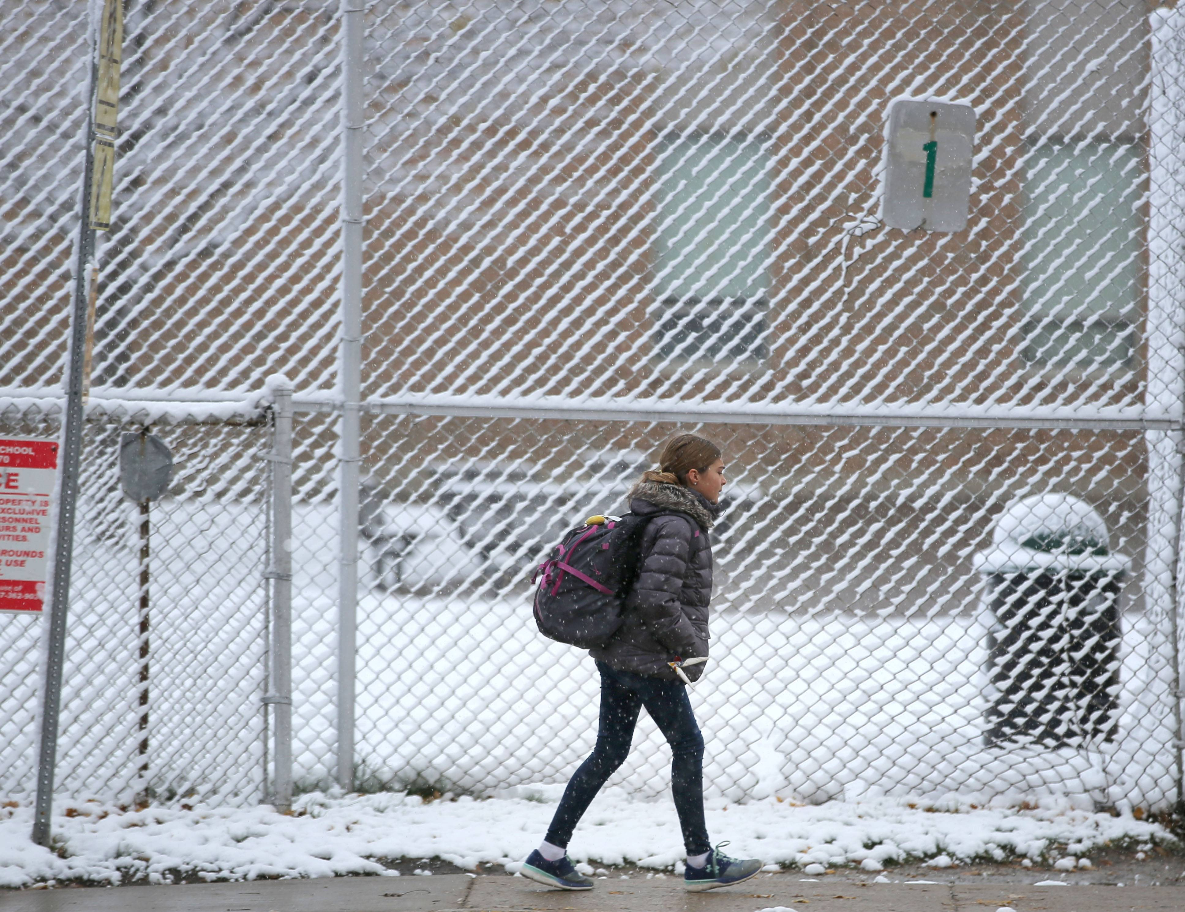 Kids head to Highland Middle School in Libertyville after an overnight snow blanketed the area Friday.
