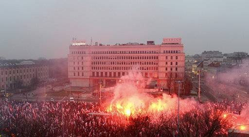 Marchers burn flares in the annual March of Independence organized by far right activists to celebrate 100 years of Poland's independence, in Warsaw, Sunday Nov. 11, 2018.  The nation of Poland regained its sovereignty at the end of World War I after being wiped off the map for more than a century.
