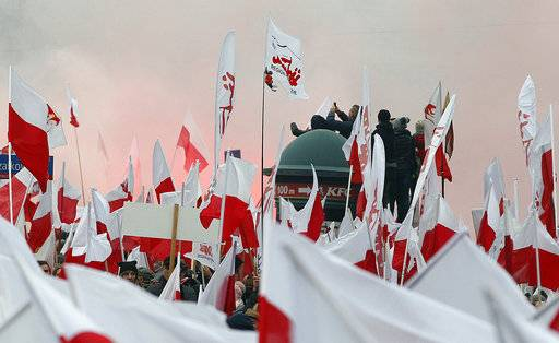 Members of radical right-wing groups light up flares during a march by tens of thousands of people and hosted by President Andrzej Duda that marked 100 years since Poland regained independence in Warsaw, Poland, Sunday, Nov. 11, 2018.