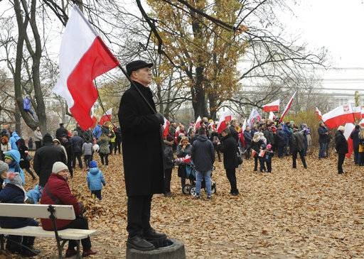 People gather in a park to watch the official ceremony marking Poland's Independence Day, in Warsaw, Poland, Sunday, Nov. 11, 2018. The Independence Day in Poland celebrates the nation regaining its sovereignty at the end of World War I after being wiped off the map for more than a century.