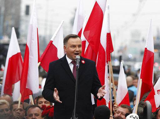 Poland's President Andrzej Duda speaks at the start of a massive march marking 100 years since Poland regained independence in Warsaw, Poland, Sunday, Nov. 11, 2018. Poland's president, prime minister and other top leaders led an Independence Day march Sunday that included members of nationalist organizations, the first time Polish state officials have marched with the far-right groups.